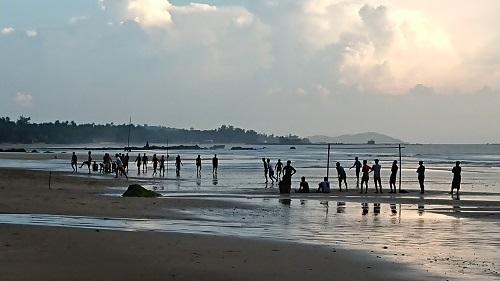 浜辺でサッカーをする現地の子供たち